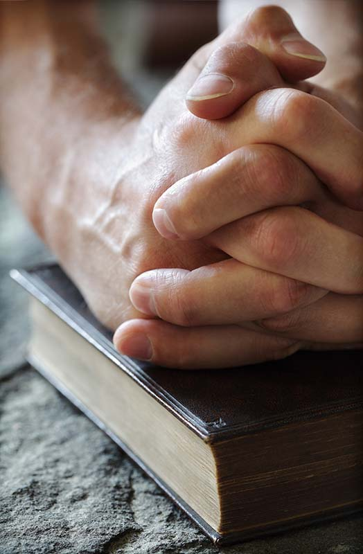 Clasped hands on a Bible resting on a solid rock in this photograph illustrate the subject We Invite You to Learn About the Church Christ Built, in iglesia-de-cristo.com.