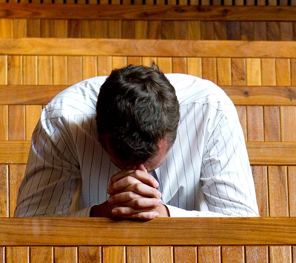 This focus on a man bowed in prayer in a church building setting illustrates the paragraph on prayer in the article We Invite You to Learn About the Church Christ Built, in iglesia-de-cristo.com.